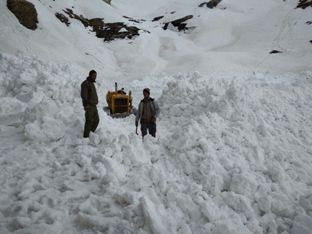 A dozer clears snow from highway near Rohtang pass.